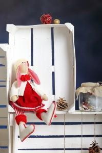 Кукла заяц сидит возле заборчика