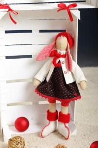 Кукла зайчиха стоит возле заборчика